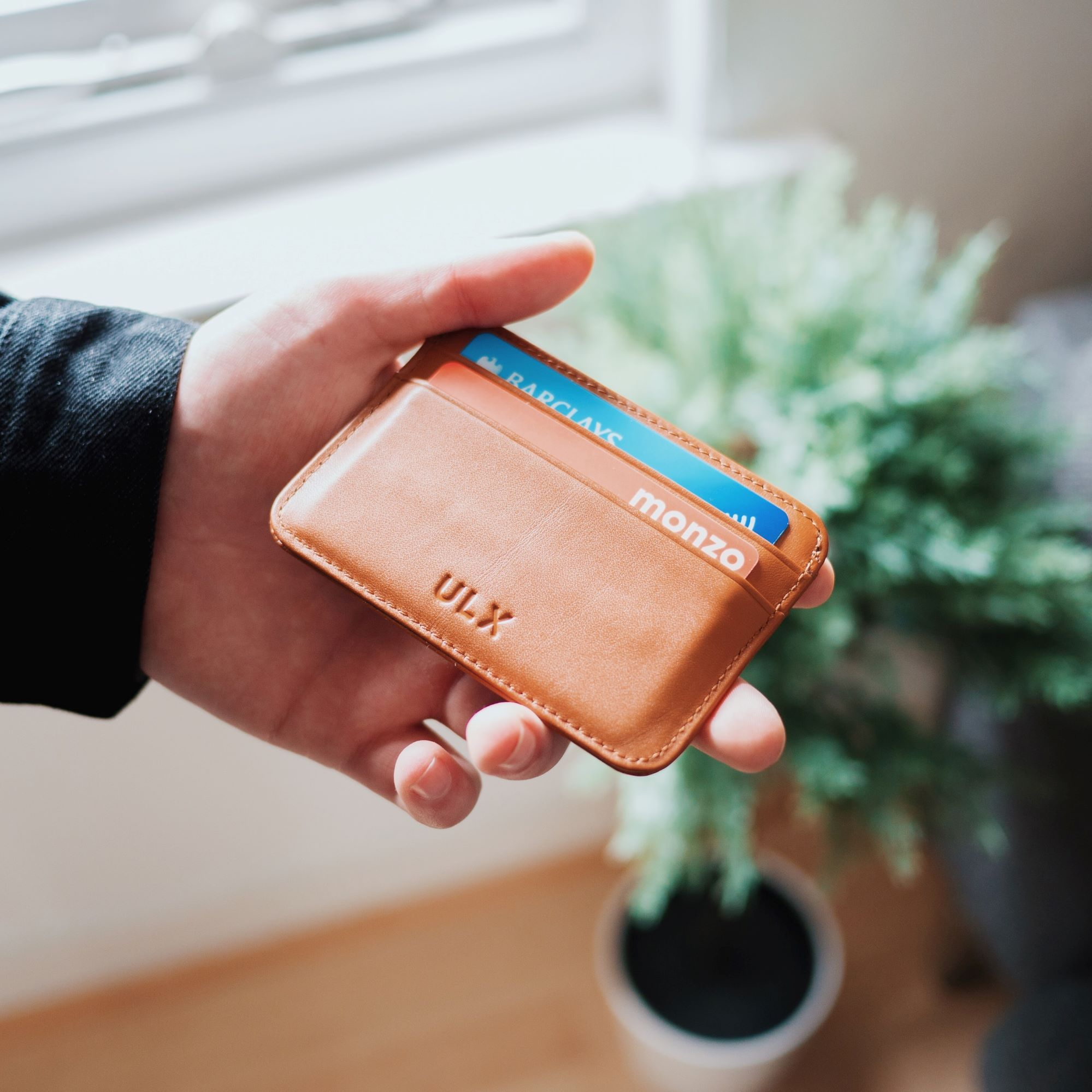 Photo of someone looking at their wallet to see if they have enough money.