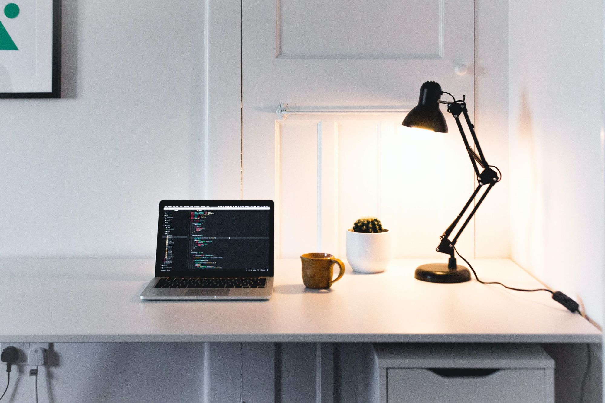 Desk with laptop, lamp, plant and coffee. A working environment